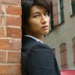 レンガの壁越しの天野浩成さん