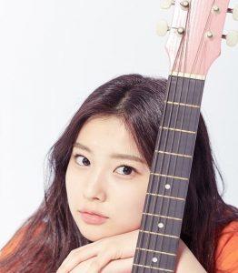 ピンクのギターの後ろに座るカンヘウォン