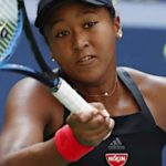 テニスの試合中でフォアハンドでボールを打つ黒いタンクトップの大坂なおみ選手