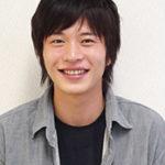 グレーのシャツに黒のインターを着た笑顔の田中圭