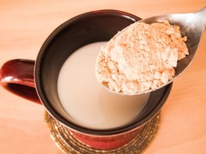 スプーンの上のきな粉と牛乳の入った赤いマグカップ
