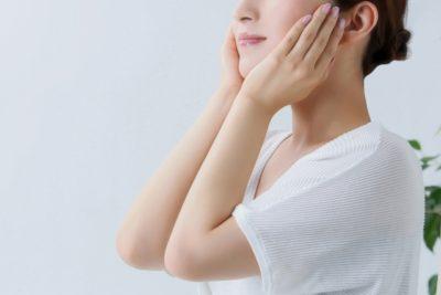 両頬を両手で包む白いシャツを着た女性