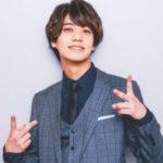 青いスーツでダブルピースをする高橋海人
