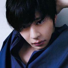 青いトップスで左手を頭の後ろに置く田中圭