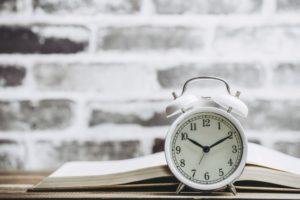白いレンガ調の壁の前の時計と本